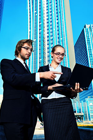 Businessman and businesswoman outside with a laptop